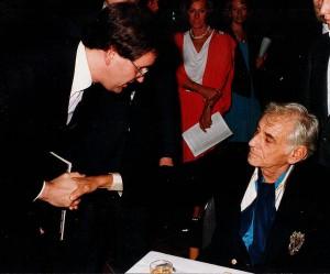 """Rainer Großimlinghaus im Gespräch mit Leonhard Bernstein anlässlich eines Konzertes der Wiener Philharmoniker am 27.10.1984 in der Düsseldorfer Tonhalle. Die soeben bei EMI erschienene LP """"Schumann-Requiem + Requiem für Mignon"""" wurde dem sehr interessierten Maestro überreicht."""