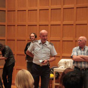 Stabshauptmann Thomas Ernst erläutert dem Chor und dem WDR-Team die Abläufe beim anstehenden Musikfest der Bundeswehr