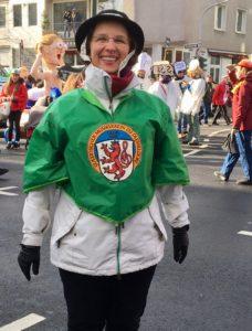 Rosenmontag - Kurz vor dem Start - Schatzmeisterin Teresia Petrik im Musikvereins-Outfit (Der grüne Umhang ist ein Regenschirm)
