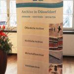 Roll-Up zur Vorstellung der Veranstaltung mit Aufzählung der Archiv-Gruppen