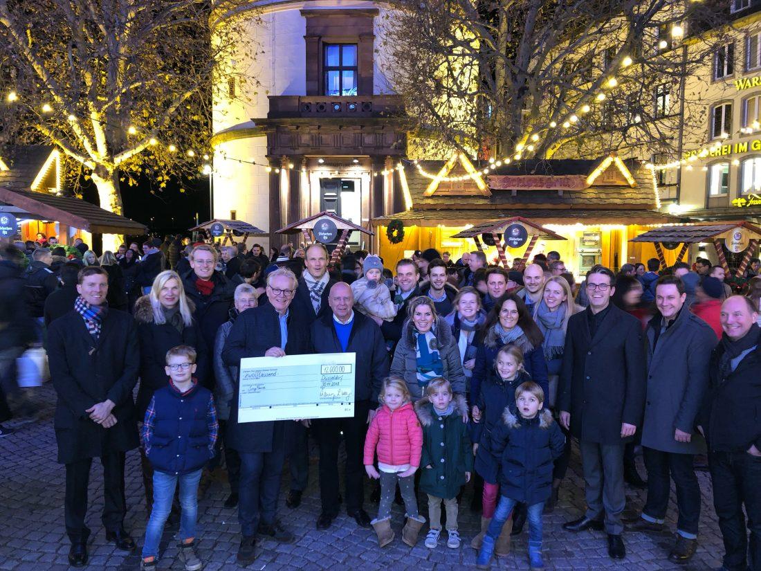 Schecküberreichung auf dem Düsseldorfer Weihnachtsmarkt mit den Mitarbeiter*innen der für die SingPause spendenden Anwaltskanzlei Rotthege und Wassermann.