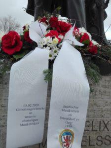 Der Städtische Musikverein erinnert am 3.2.2020 an den Geburtstag seines ehemaligen Musikdirektors mit einem Blumengesteck an seinem Denkmal